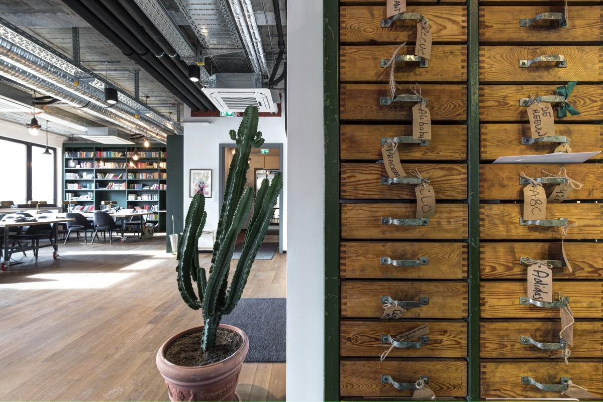 Die Postfächer am Empfang (rechts) sind Schubläden, links in der Tiefe sind die Coworking-Desks mit einem riesigen Bücherregal an der Wand. (Foto: Mindspace)